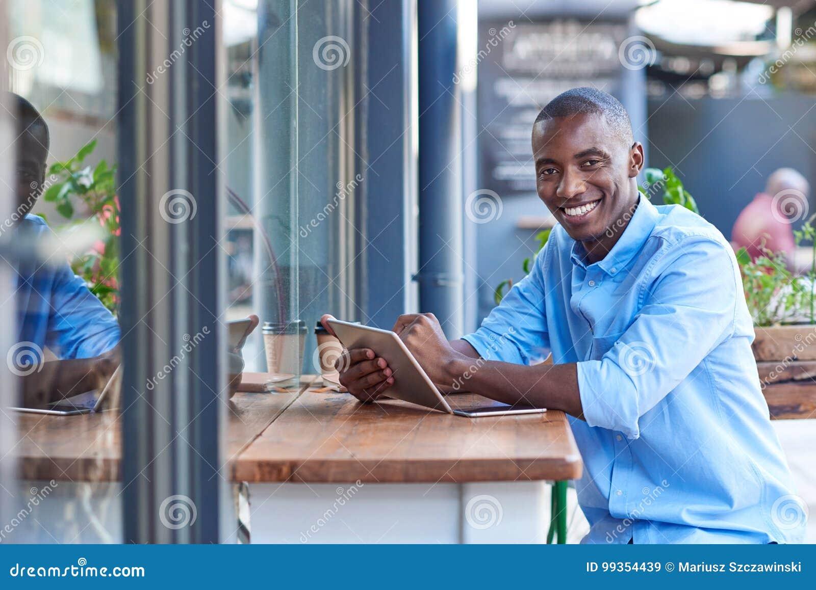 Le den afrikanska mannen som direktanslutet arbetar på en trottoarkaféräknare