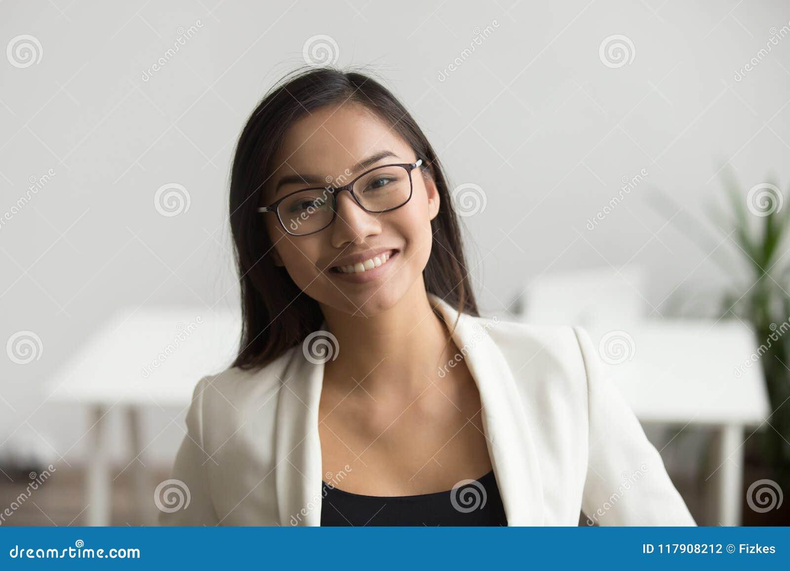 Le den asiatiska kvinnan i exponeringsglas som ser kameran, headshotportr