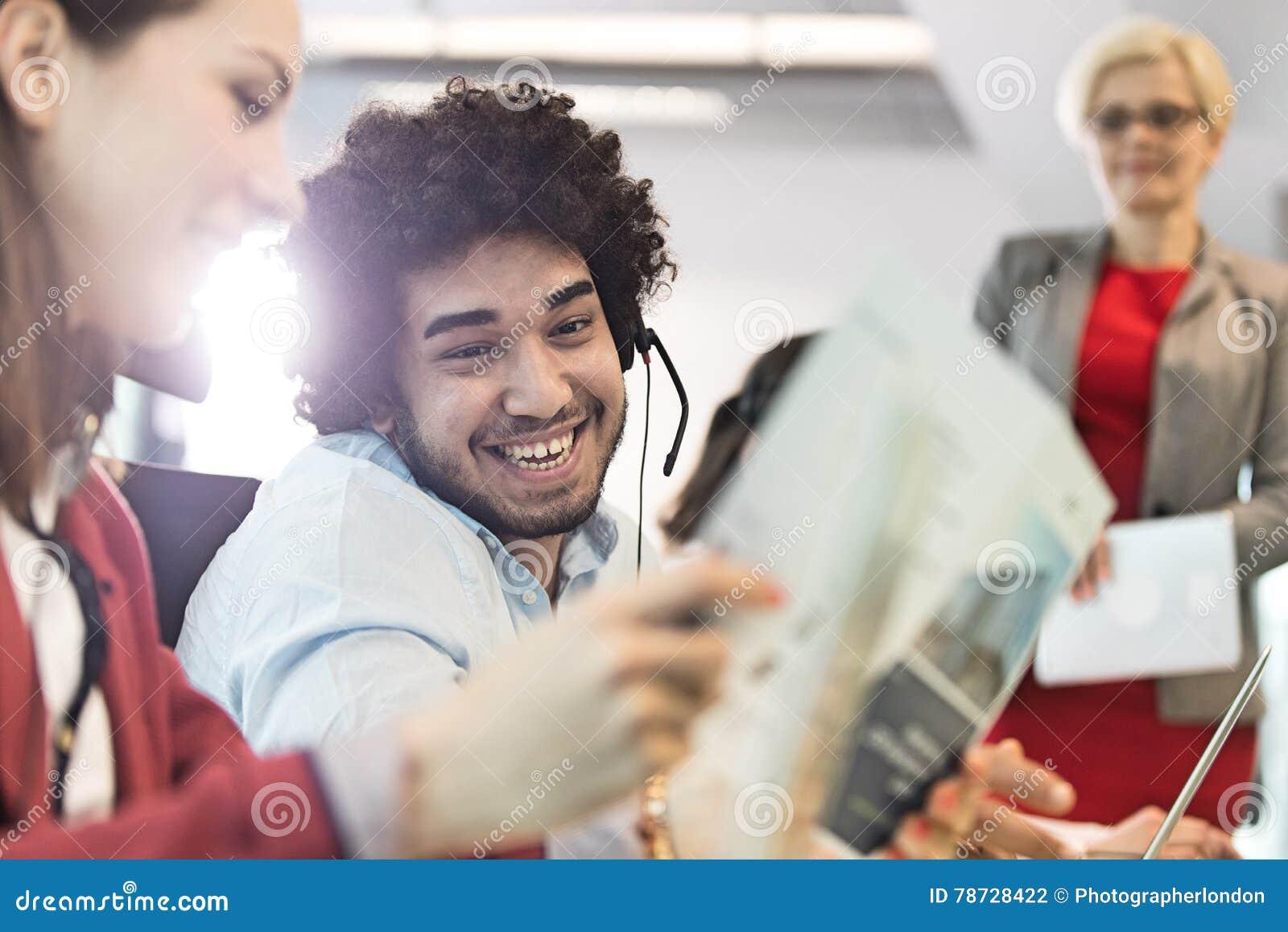 Le den bärande hörlurar med mikrofon för ung affärsman med kollegor i regeringsställning