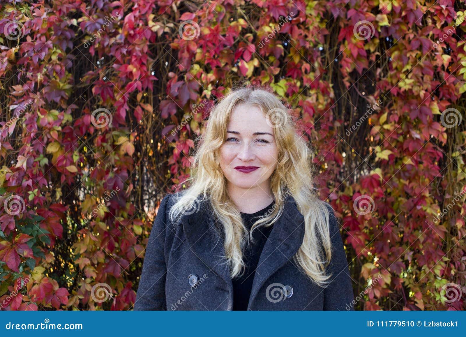 Le den blonda kvinnan nära färgrika sidor
