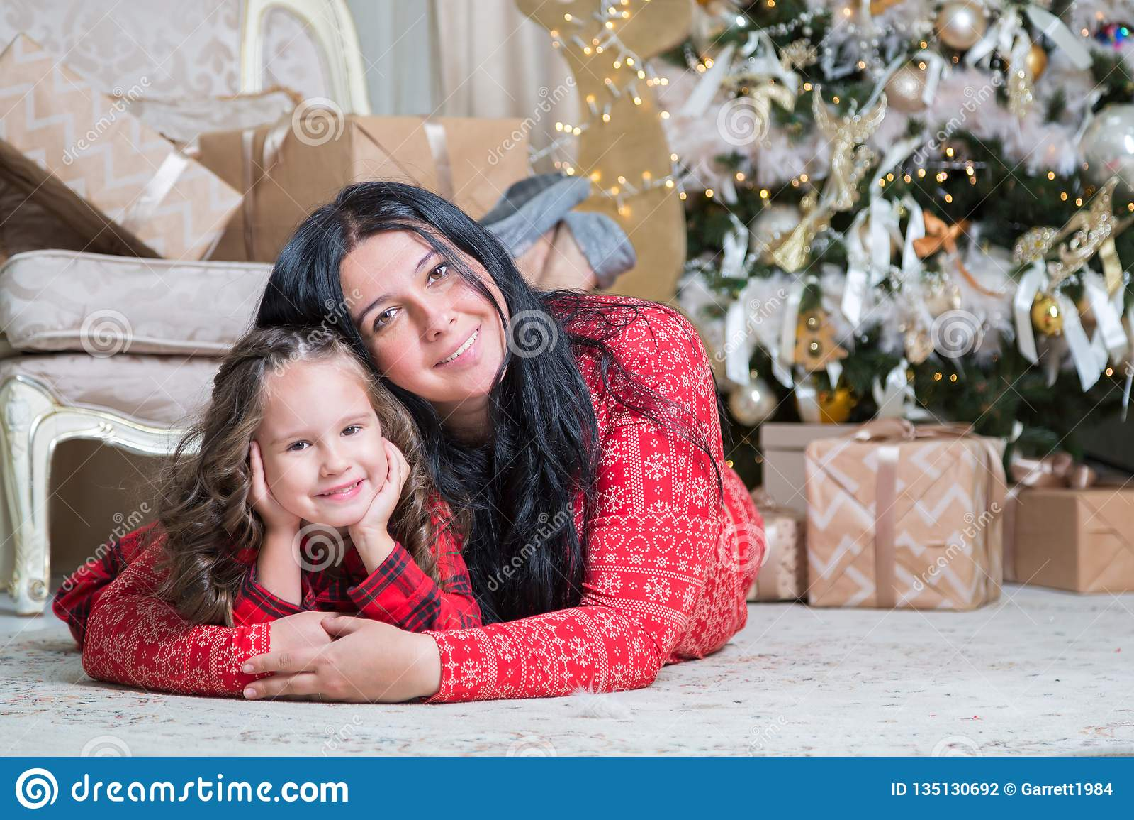 Le den gulliga lilla flickan med modern nära gåvor och julgranen Nytt år eller julfamiljberöm hemma