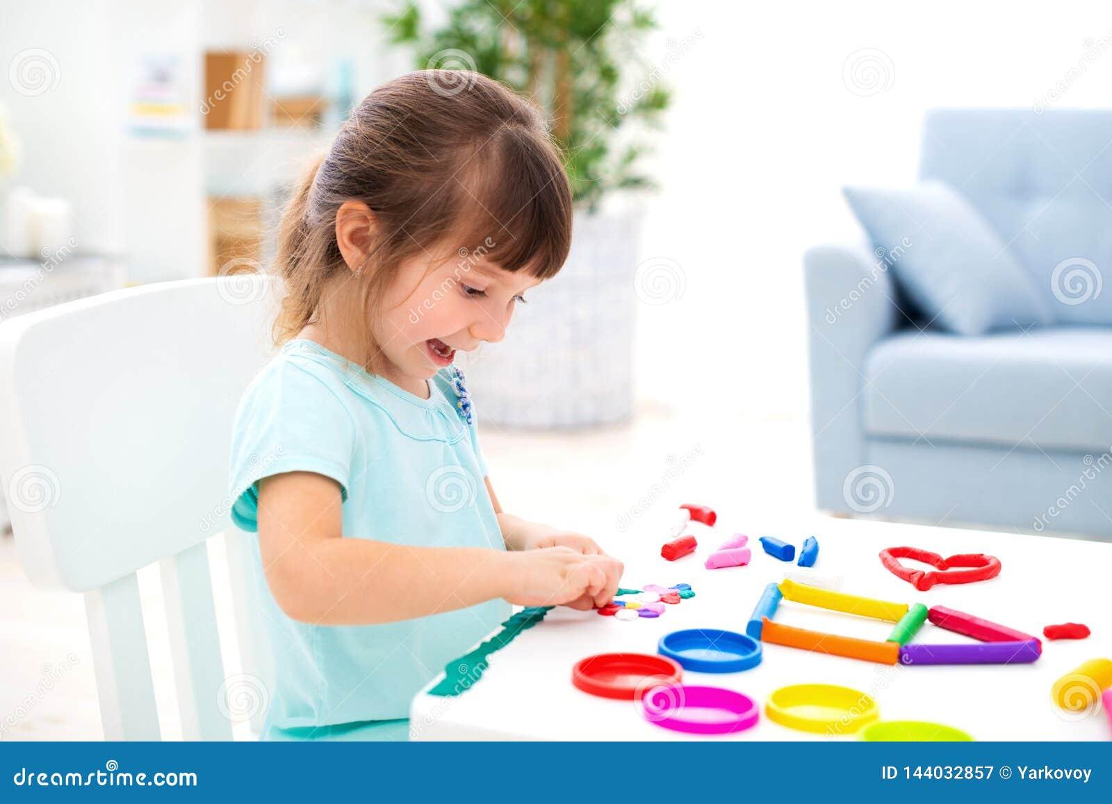 Le den lilla härliga flickan för att hugga det nya huset av plasticine Barnkreativitet lycklig barndom Inflyttnings- drömmar