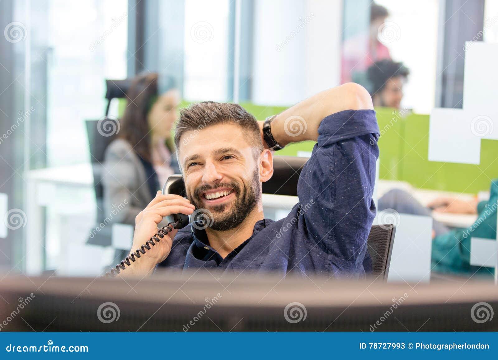 Le den mitt- vuxna affärsmannen som i regeringsställning talar på telefonen