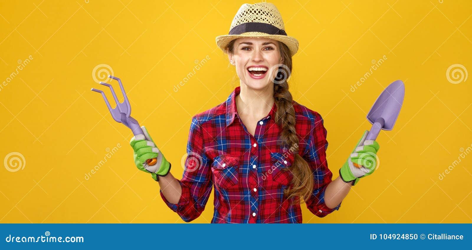 Le den moderna kvinnabondevisningen som arbeta i trädgården hjälpmedel