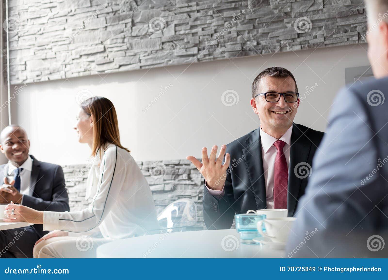 Le den mogna mannen som i regeringsställning talar med den manliga kafeterian för kollega