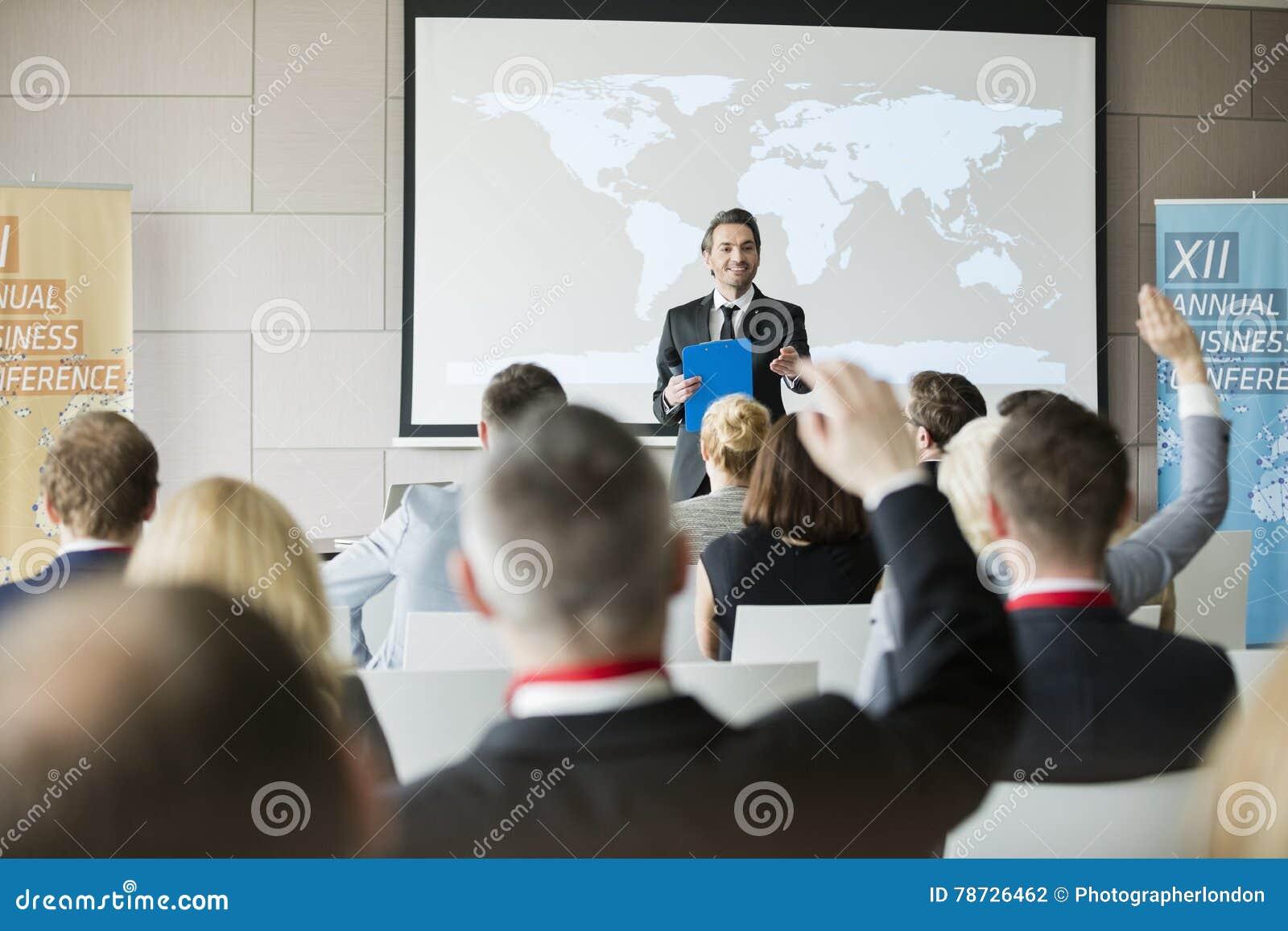 Le den offentliga högtalaren som frågar frågor till åhörare under seminarium