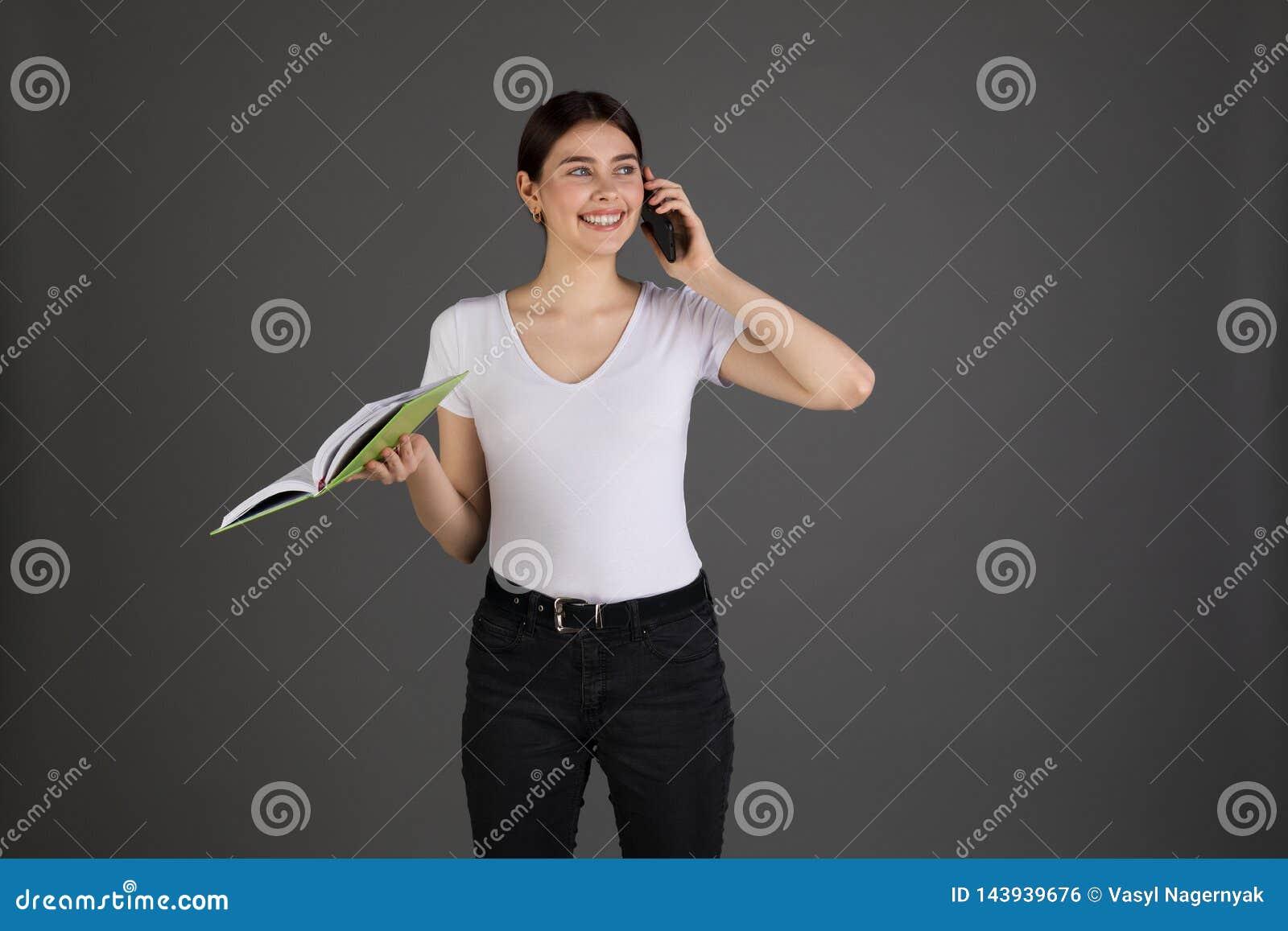 Le den positiva brunettaffärskvinnan i den vita t-skjortan