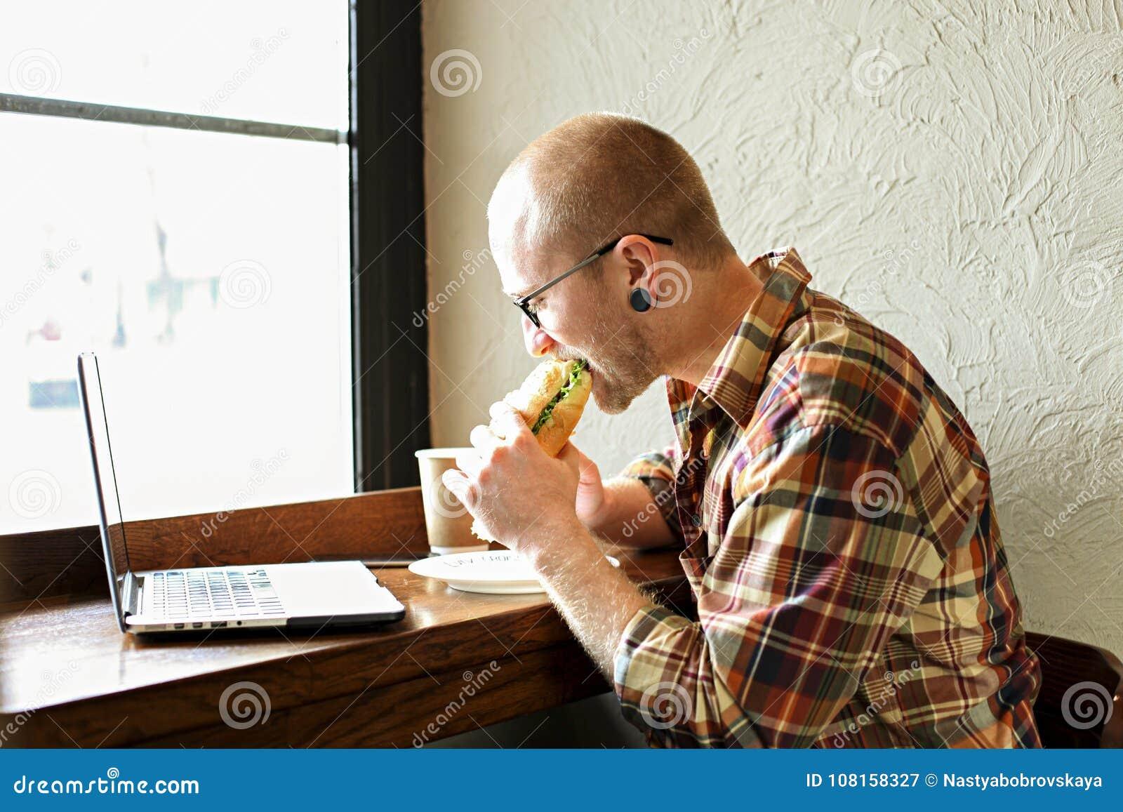 Le den skäggiga affärsmannen som bär tillfälliga hipsterkläder genom att använda bärbar dator- och cellsmartphonen i coffehus