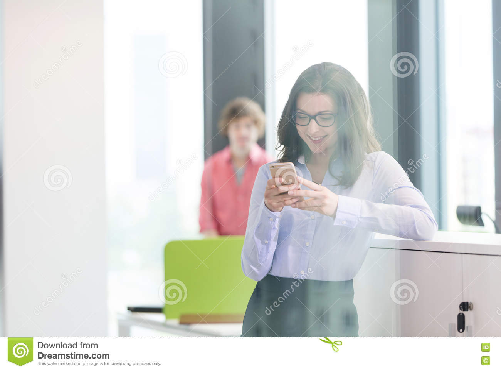 Le den unga affärskvinnan som använder mobiltelefonen med den manliga kollegan i bakgrund på kontoret