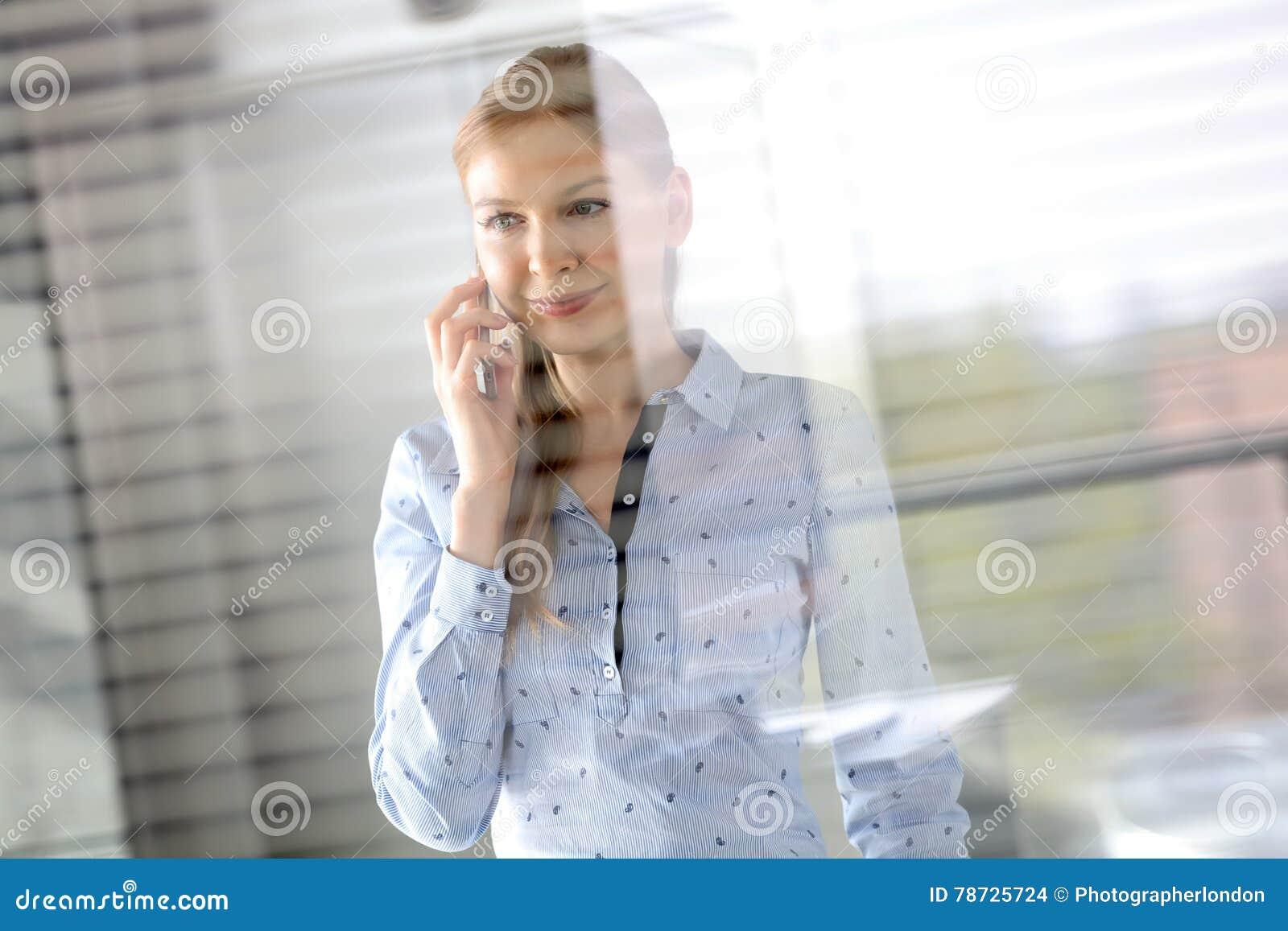 Le den unga affärskvinnan som använder mobiltelefonen på kontoret