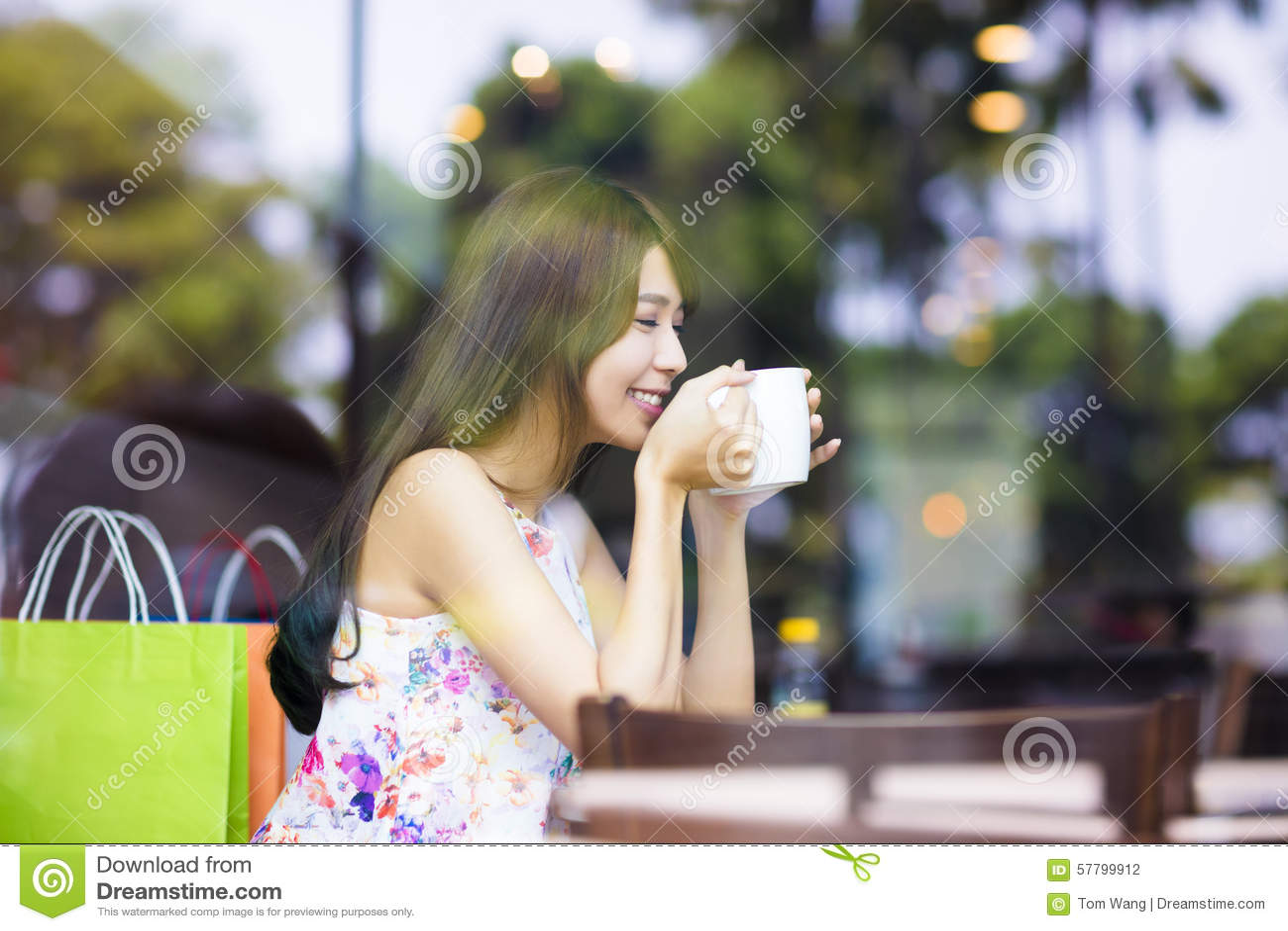 Le den unga kvinnan som dricker kaffe i kafé, shoppa
