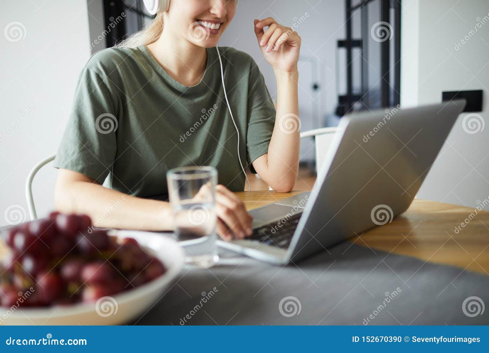 Le den unga kvinnan som framme knyter kontakt av bärbara datorn