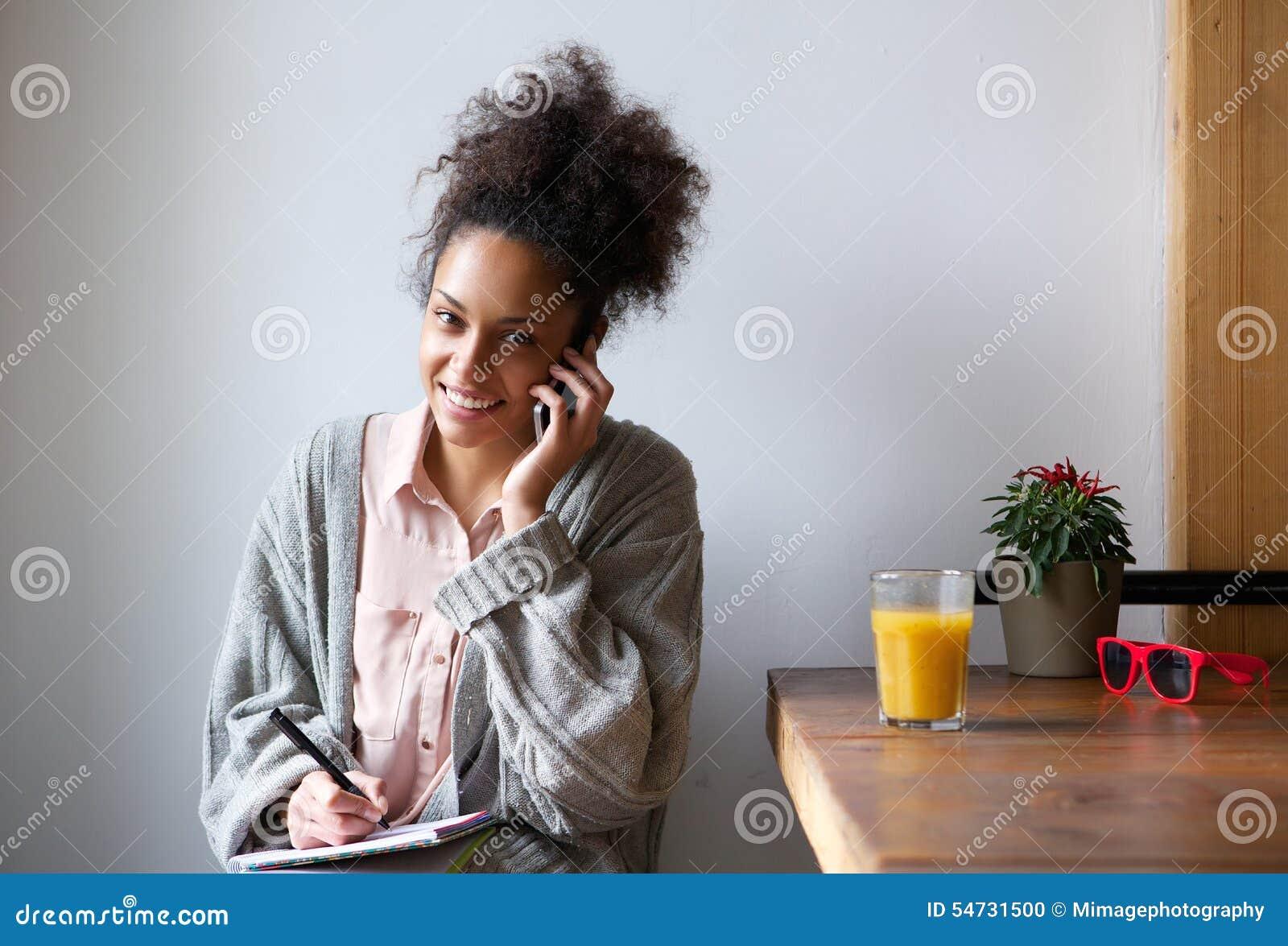 Le den unga kvinnan som tar anmärkningar med pennan och pappers- hemmastatt