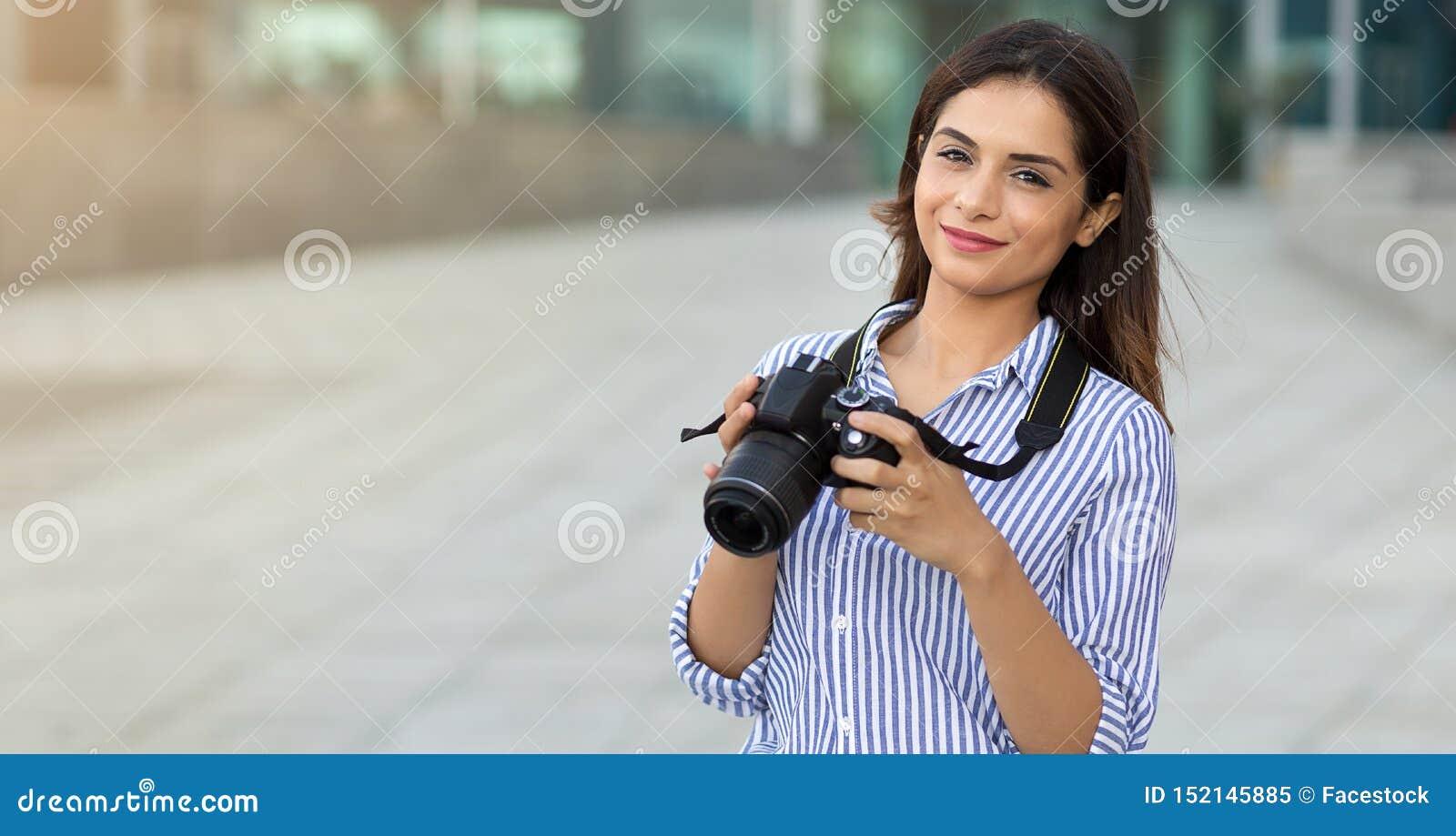 Le den unga kvinnan som utomhus rymmer kameran med kopieringsutrymme Fotograf turist