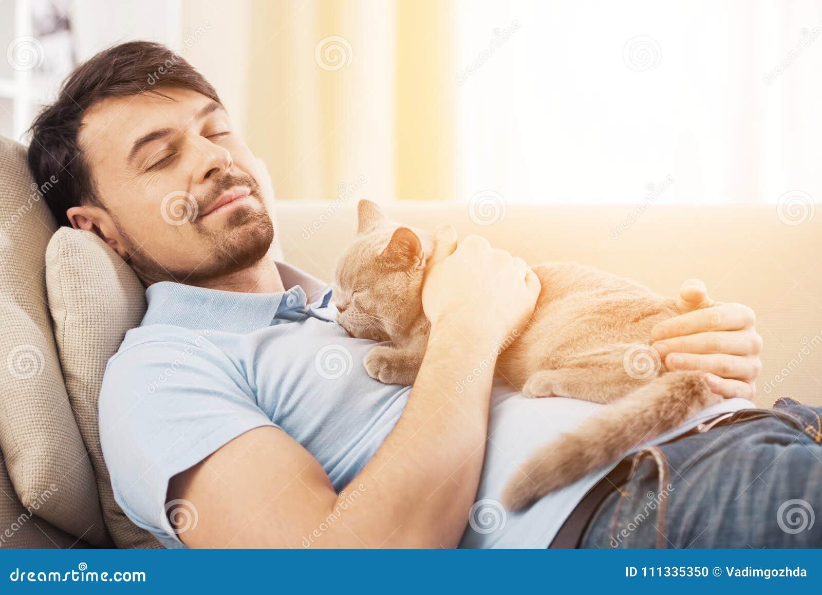 Le den unga mannen med hans gulliga katt på soffan hemma