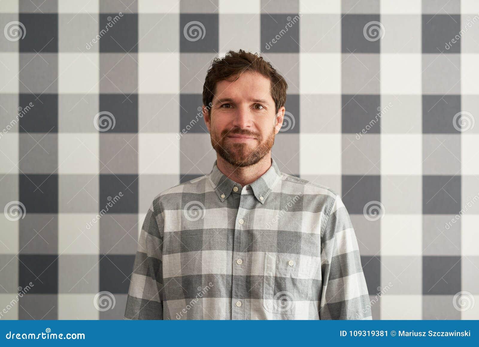 Le den unga mannen som bär en rutig skjorta som matchar hans tapet