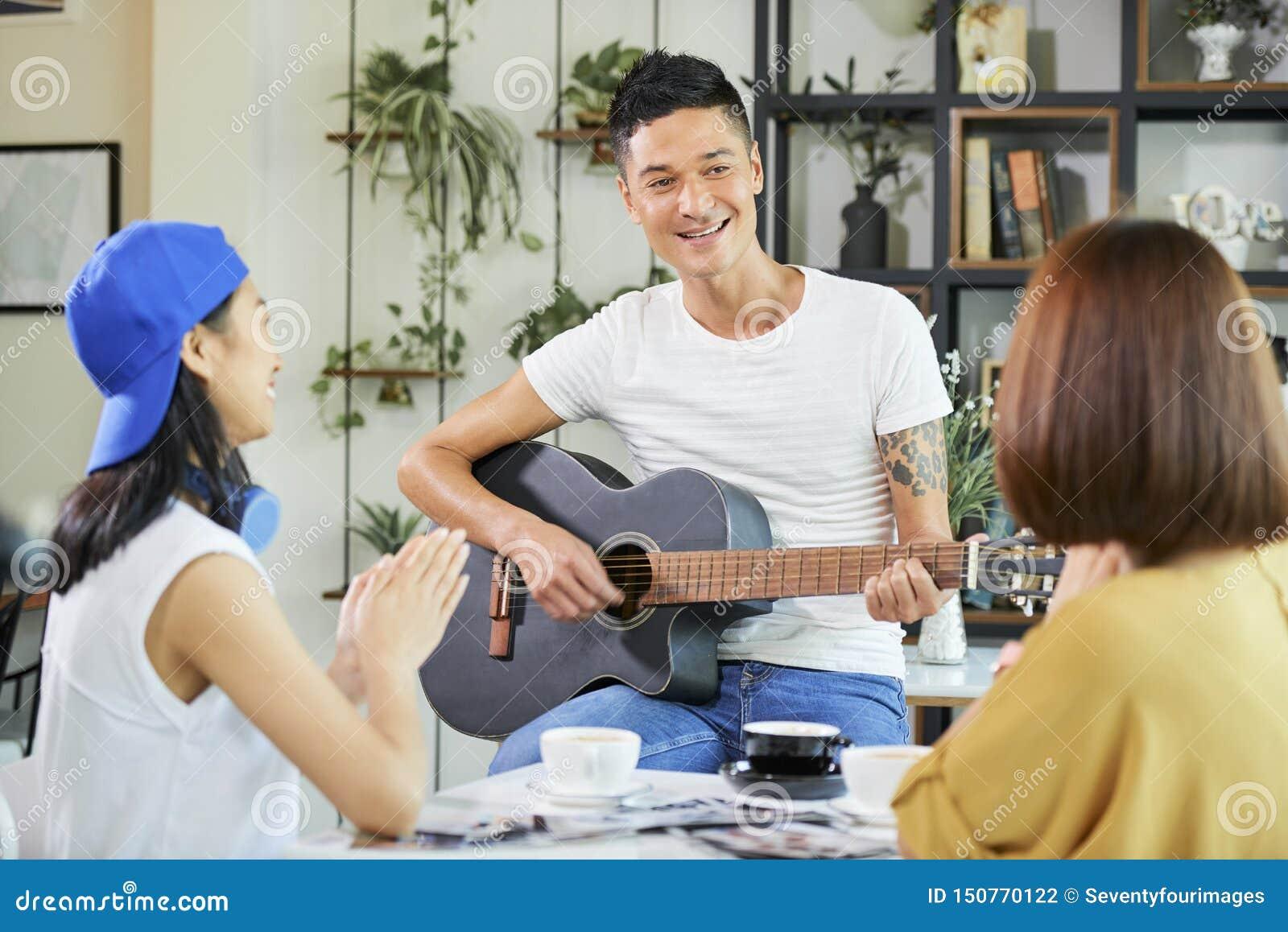 Le den unga mannen som spelar gitarren för vänner