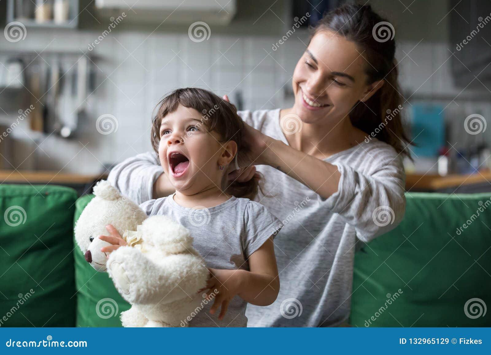 Le den unga mumen som gör hästsvansen till den lilla dottern