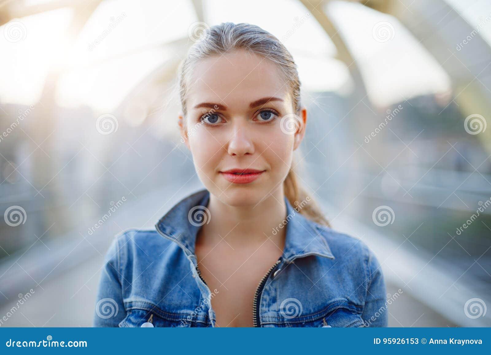Le den vita Caucasian flickakvinnan med ponnysvansen, bärande jeansomslag utanför i bro för gata för aftonnattstad