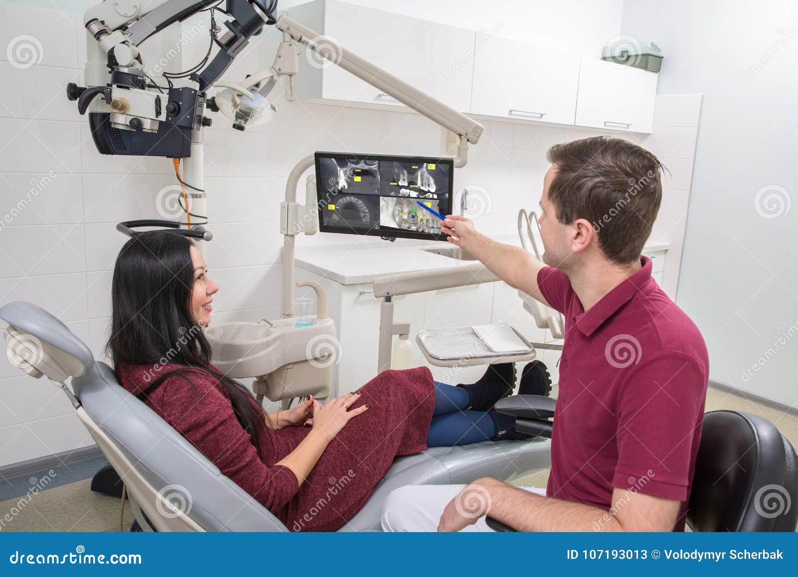 Le dentiste montre un rayon X patient des dents Clinique dentaire Le patient s assied dans une chaise le dentiste dirige la poign