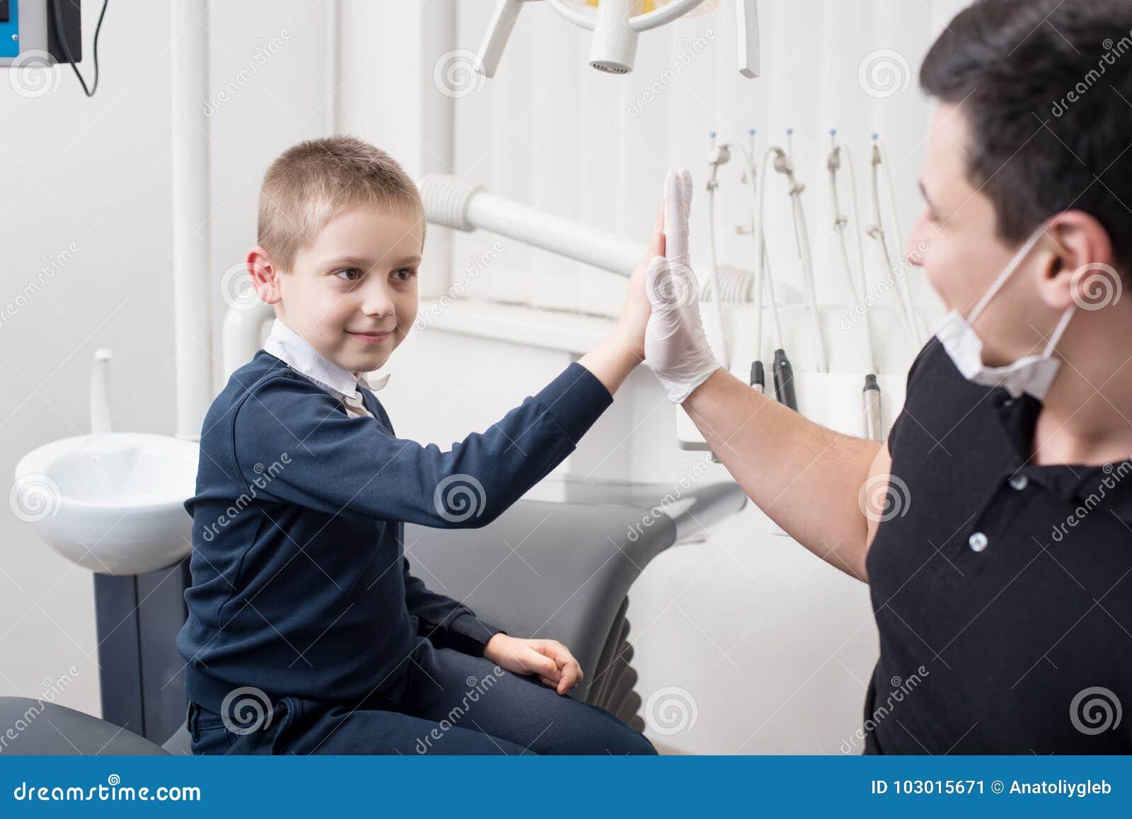 Le dentiste pédiatrique serrent la main au jeune garçon