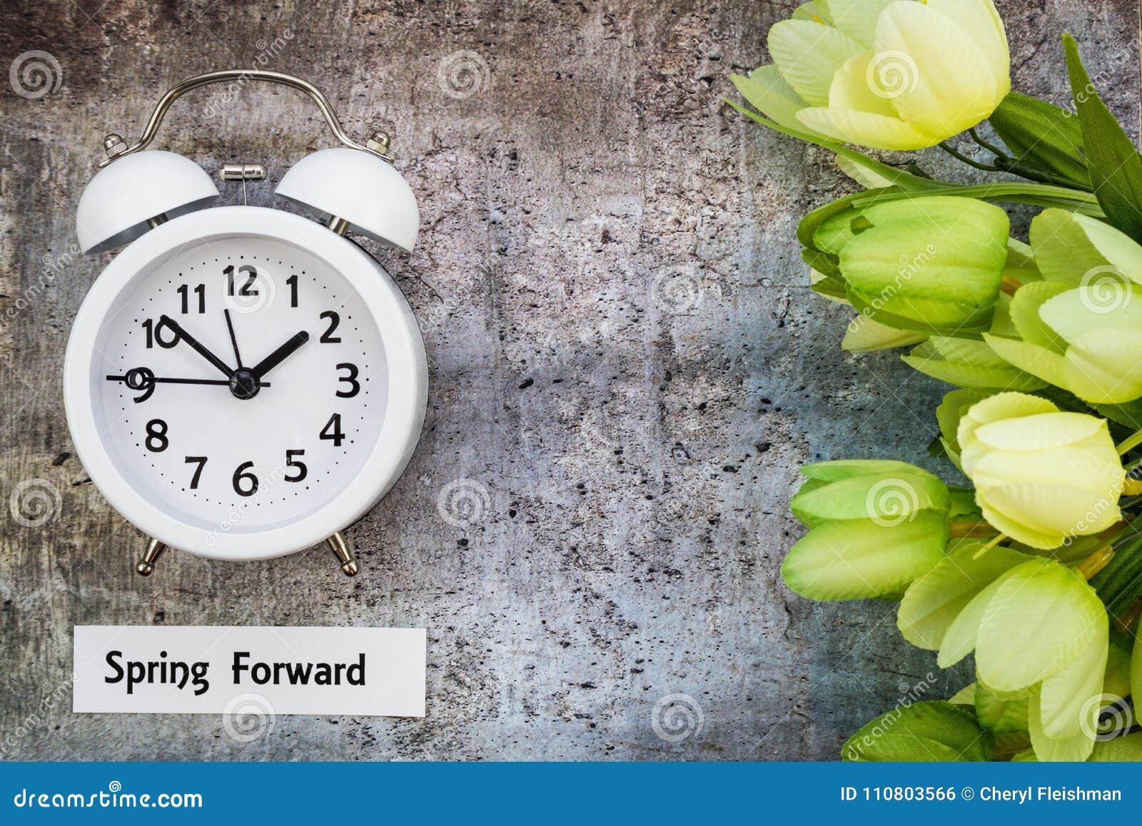 Le dessus en avant de concept de ressort de temps heures d été regardent vers le bas avec l horloge blanche et les tulipes vertes