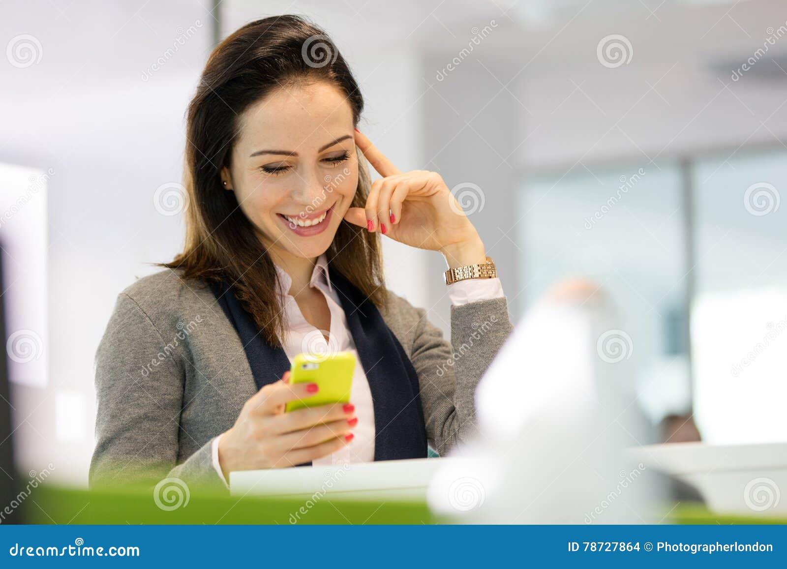 Le det läs- textmeddelandet för ung affärskvinna på smartphonen på kontoret