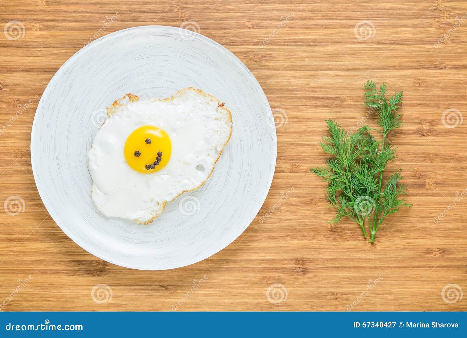 Le det stekte ägget som ligger på en vit platta på en träskärbräda med gruppen av dill Klassiskt frukostbegrepp