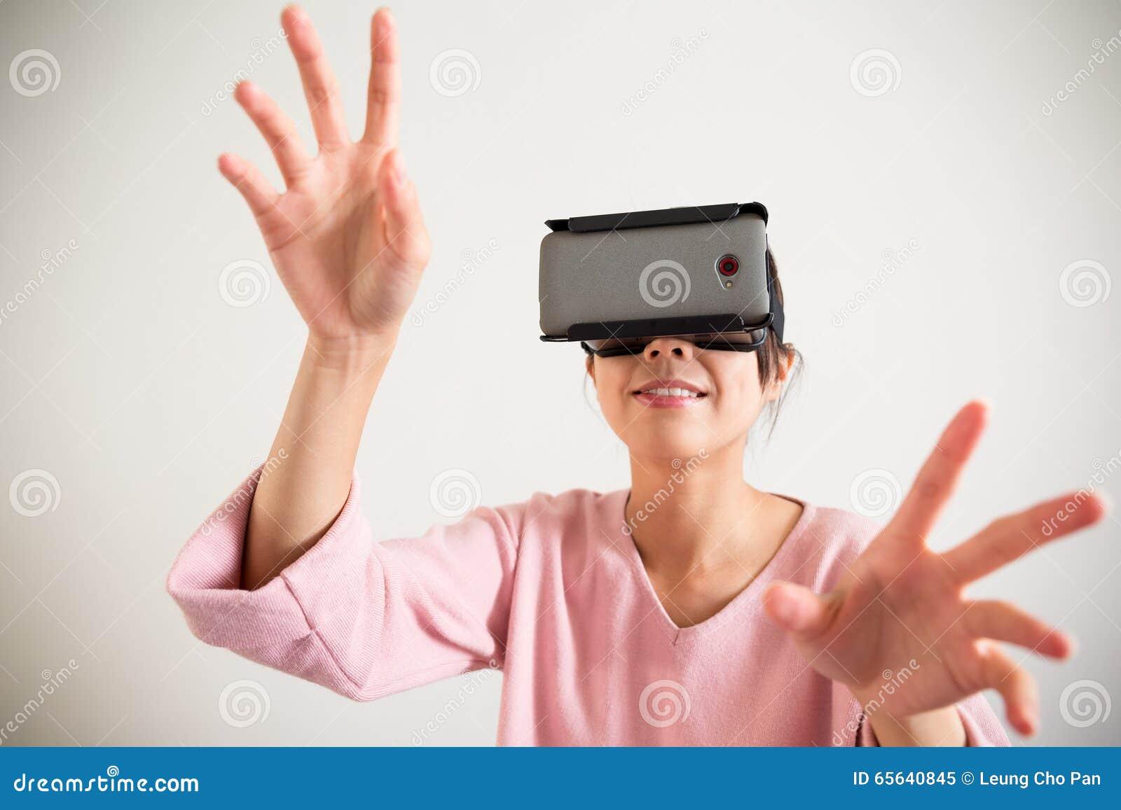 Le dispositif et la main de port de vr de jeune femme veulent toucher le somrth