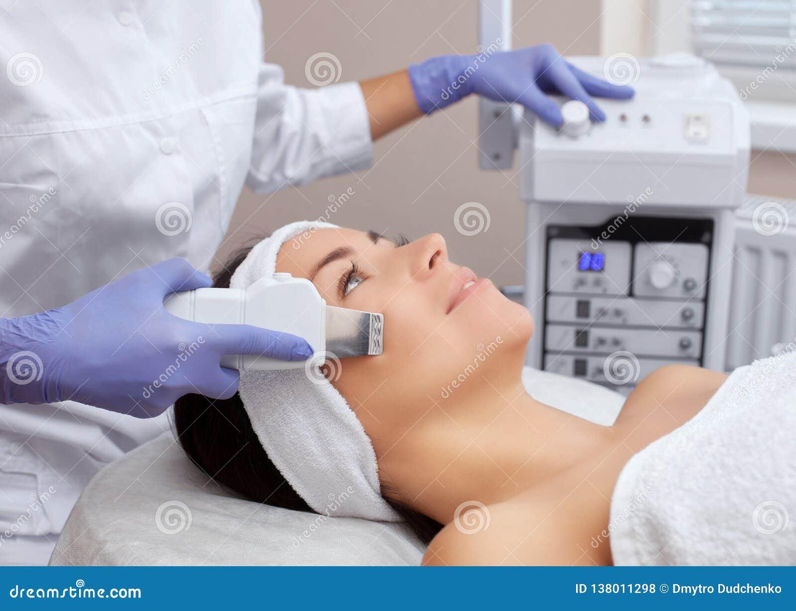 Le docteur-cosmetologist fait la procédure de nettoyage d ultrason de la peau faciale