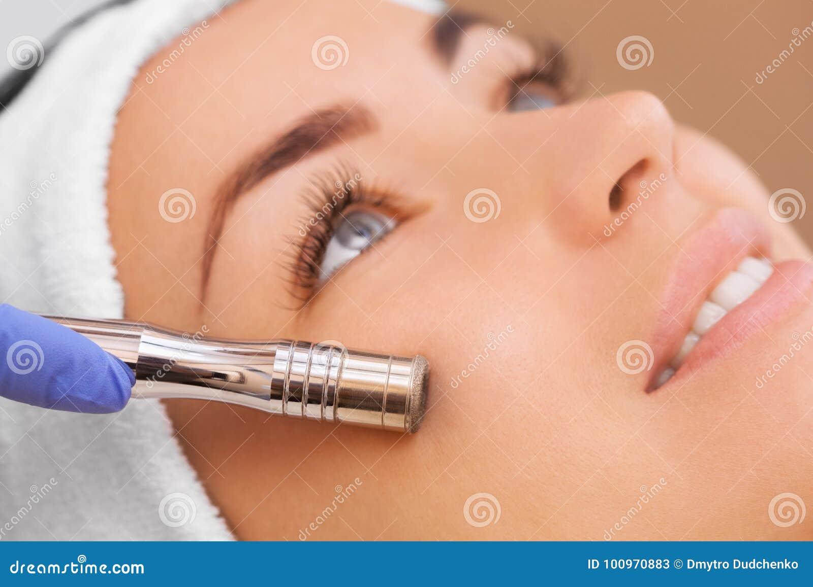 Le docteur-cosmetologist fait la procédure Microdermabrasion de la peau faciale d un beau, jeune femme dans un salon de beauté
