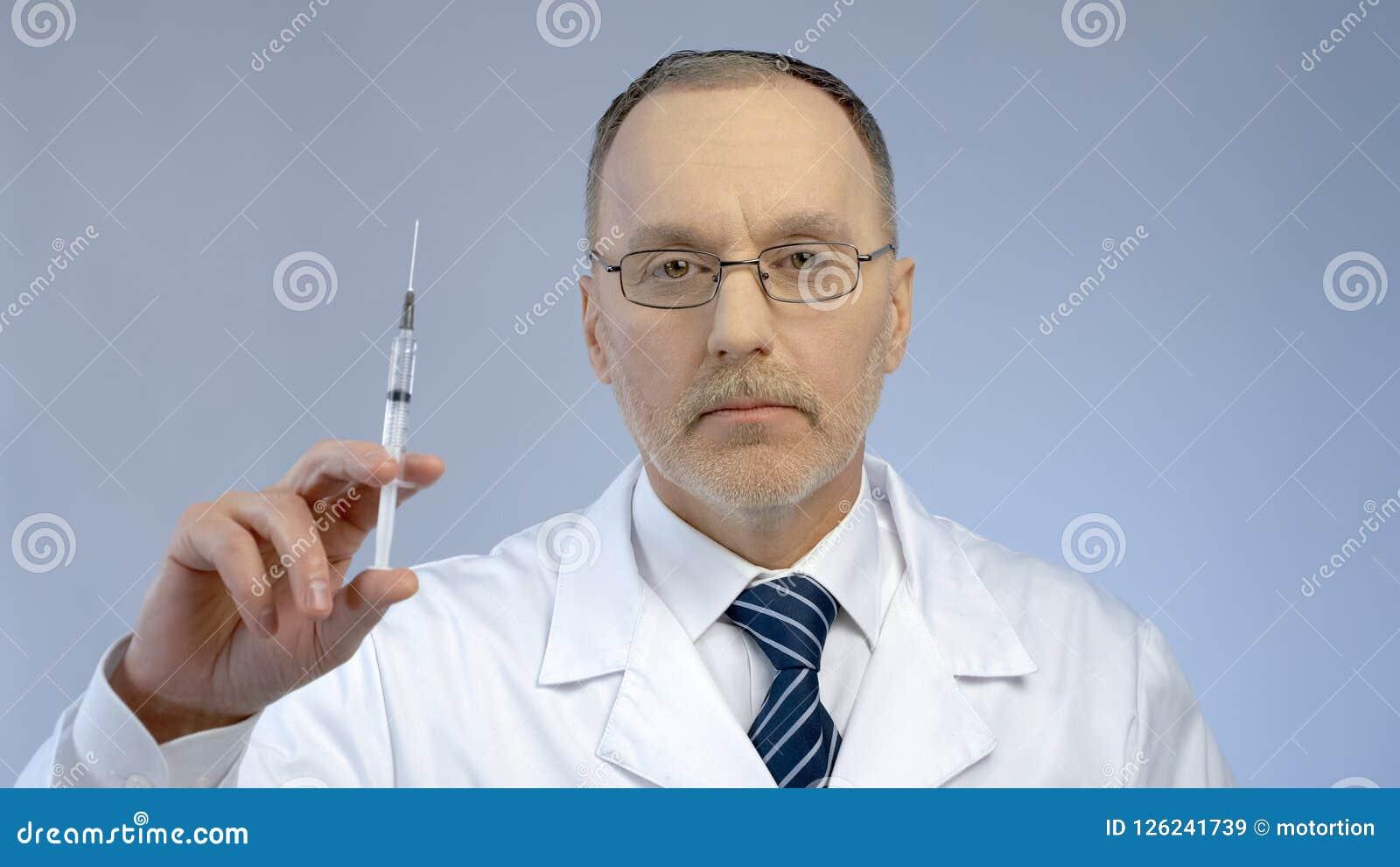 Le docteur sérieux tenant la seringue, préparent pour faire l injection vaccinique, épidémie de grippe