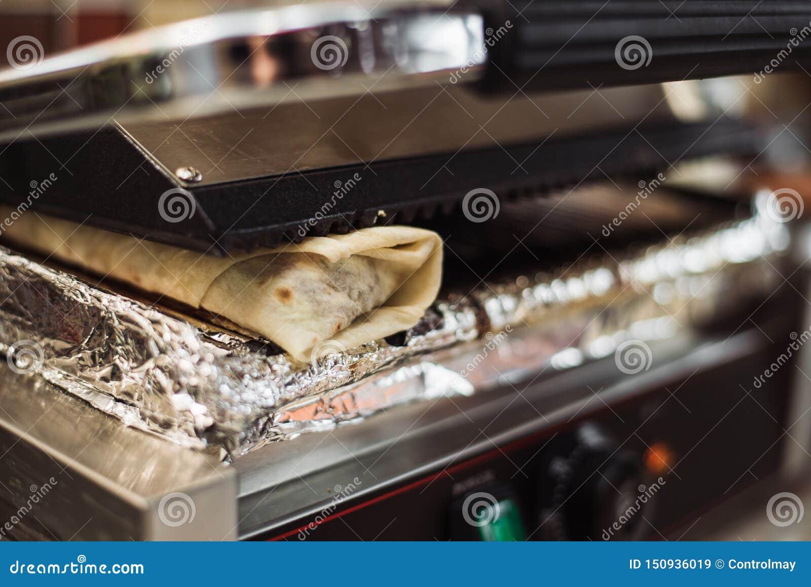 Le doner de Shawarma a fait cuire au four dans un four électrique dans un restaurant d aliments de préparation rapide