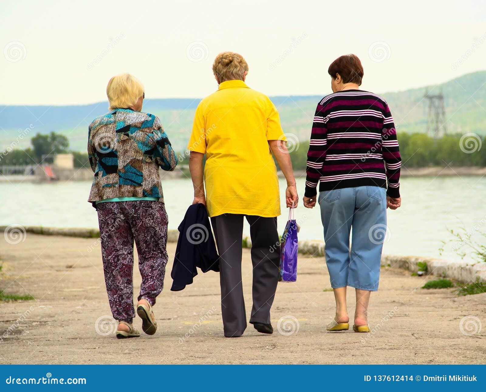 Le donne anziane camminano lungo l argine
