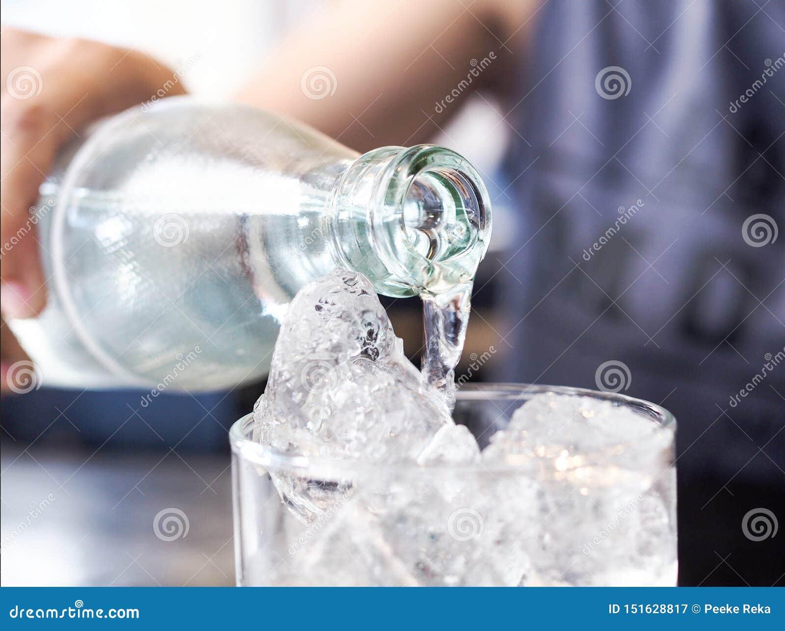 Le donne asiatiche stanno versando l acqua potabile pulita in vetro del ghiaccio