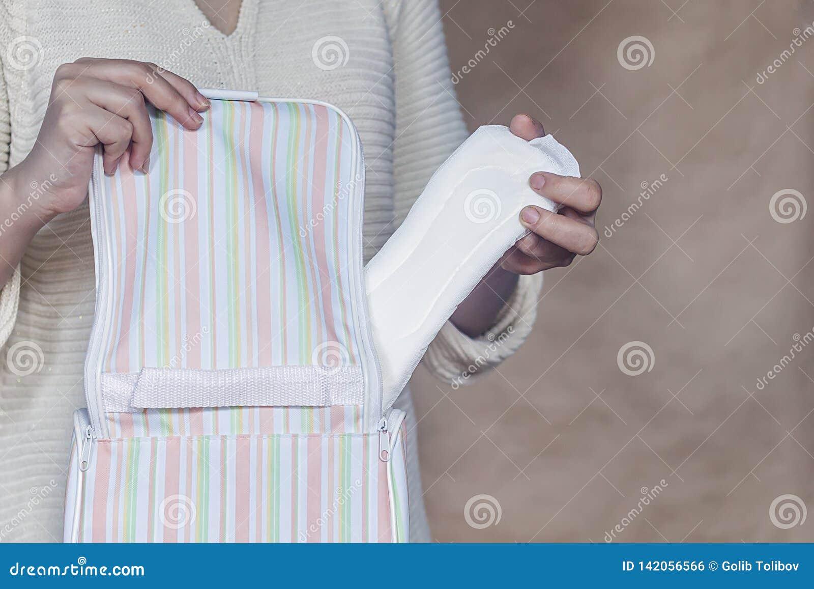 Le donne tengono un cuscinetto mestruale Giovane donna che elimina un cuscinetto sanitario dalla sua borsa Cuscinetto mestruale b
