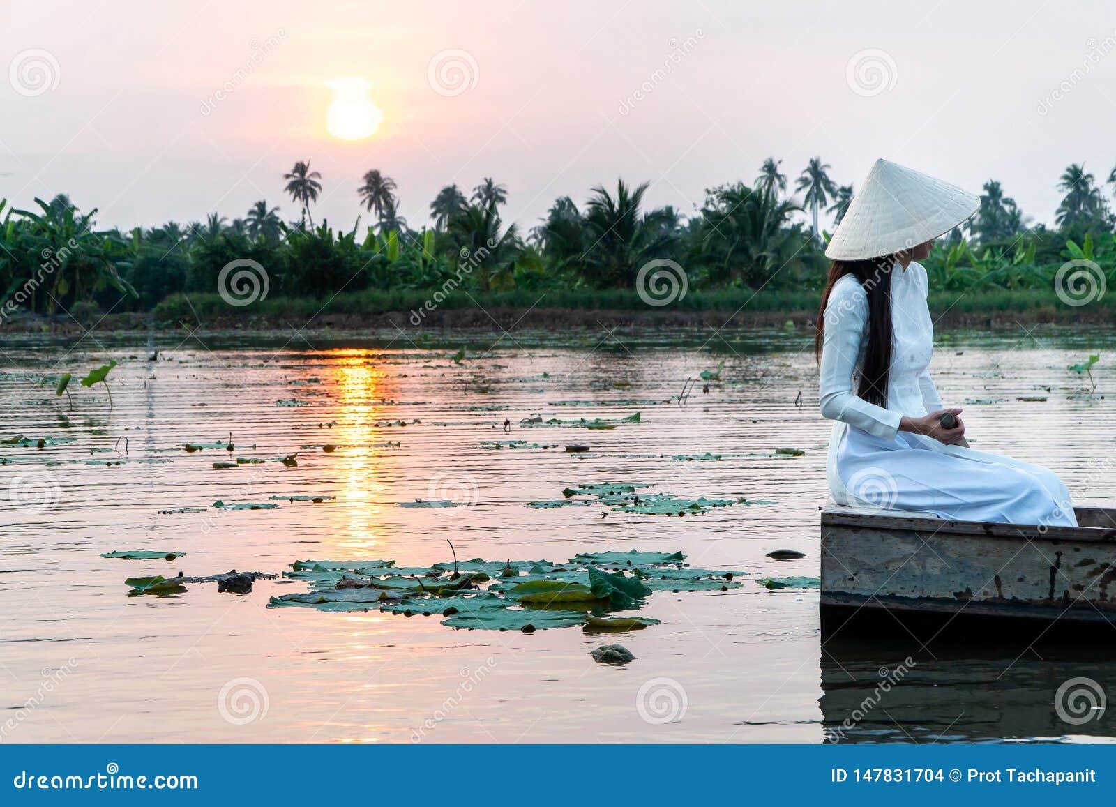 Le donne turistiche che portano il cappello tradizionale bianco del vestito Ao Wai del Vietnam e dell agricoltore del Vietnam e c