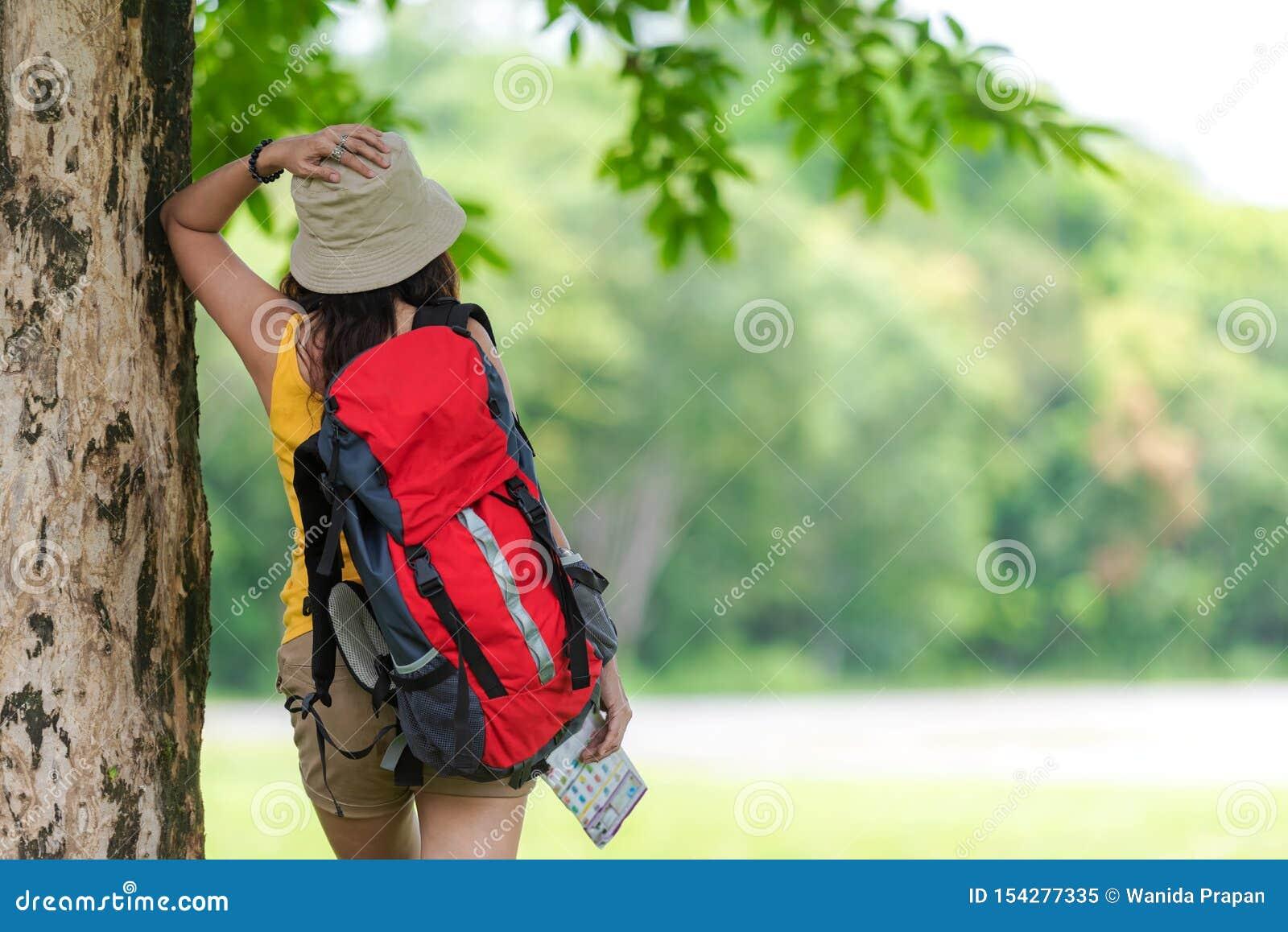 Le donne viandante o viaggiatore con la mappa della tenuta di avventura dello zaino per trovare le direzioni e la camminata si ri