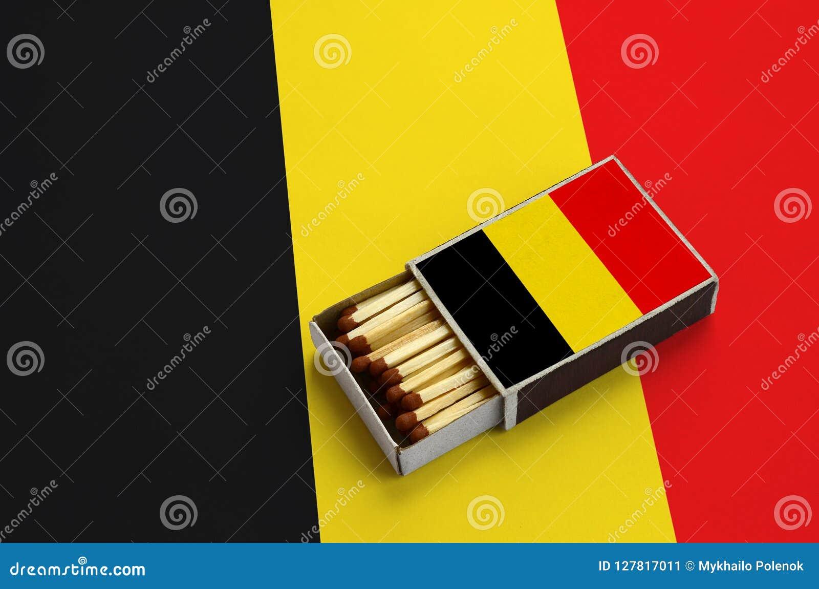 Le drapeau de la Belgique est montré dans une boîte d allumettes ouverte, qui est remplie de matchs et se trouve sur un grand dra