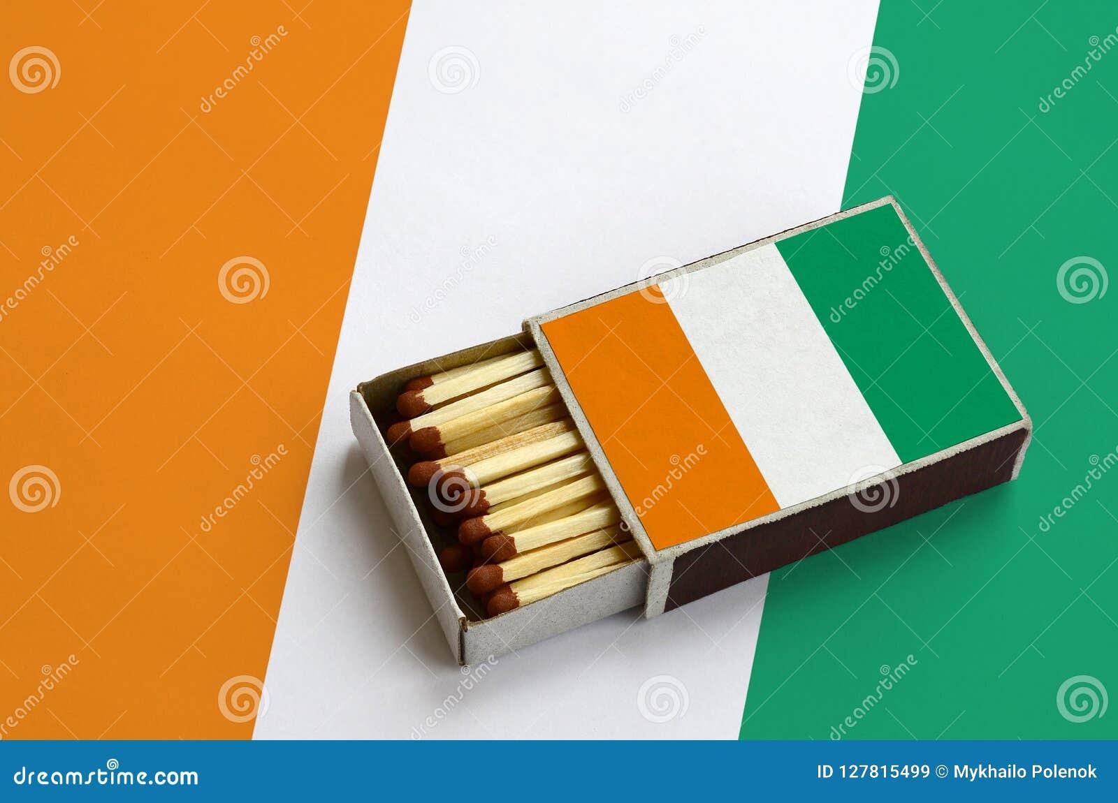 Le drapeau de la Côte d Ivoire est montré dans une boîte d allumettes ouverte, qui est remplie de matchs et se trouve sur un gran