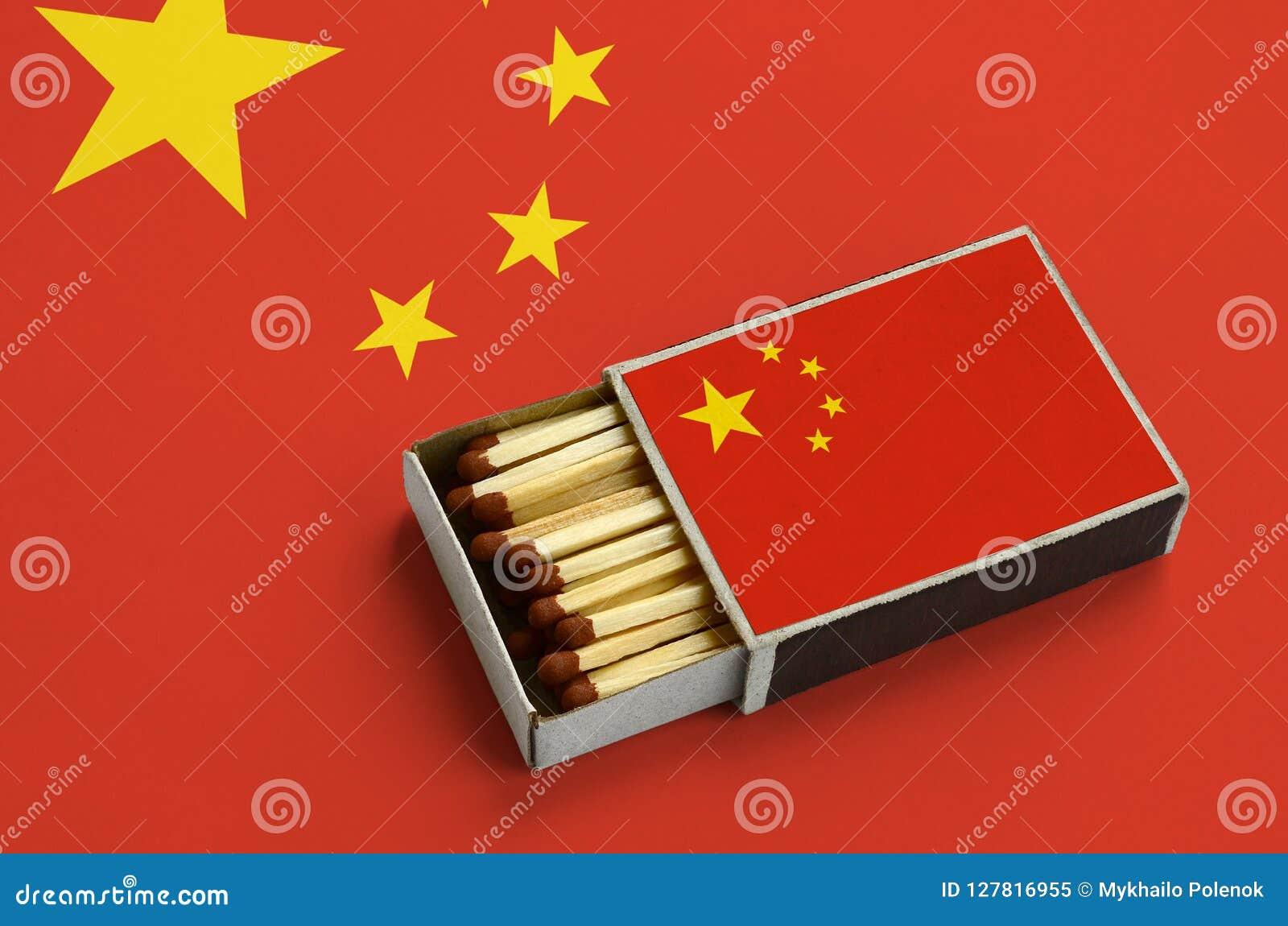 Le drapeau de la Chine est montré dans une boîte d allumettes ouverte, qui est remplie de matchs et se trouve sur un grand drapea