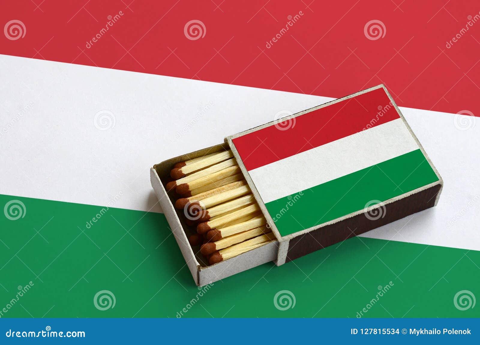 Le drapeau de la Hongrie est montré dans une boîte d allumettes ouverte, qui est remplie de matchs et se trouve sur un grand drap
