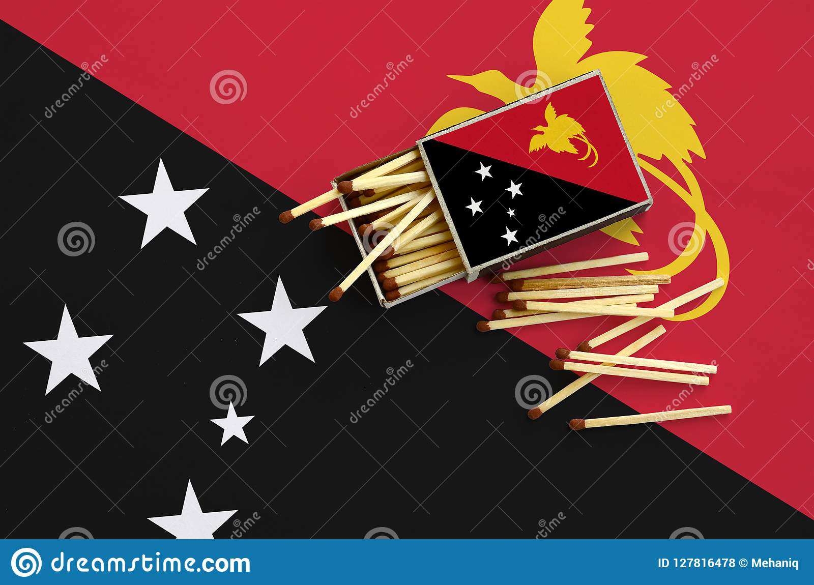 Le drapeau de la Papouasie-Nouvelle-Guinée est montré sur une boîte d allumettes ouverte, de laquelle plusieurs matchs tombent et