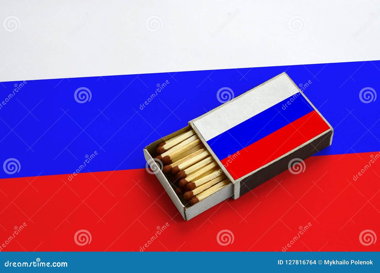 Le drapeau de la Russie est montré dans une boîte d allumettes ouverte, qui est remplie de matchs et se trouve sur un grand drape