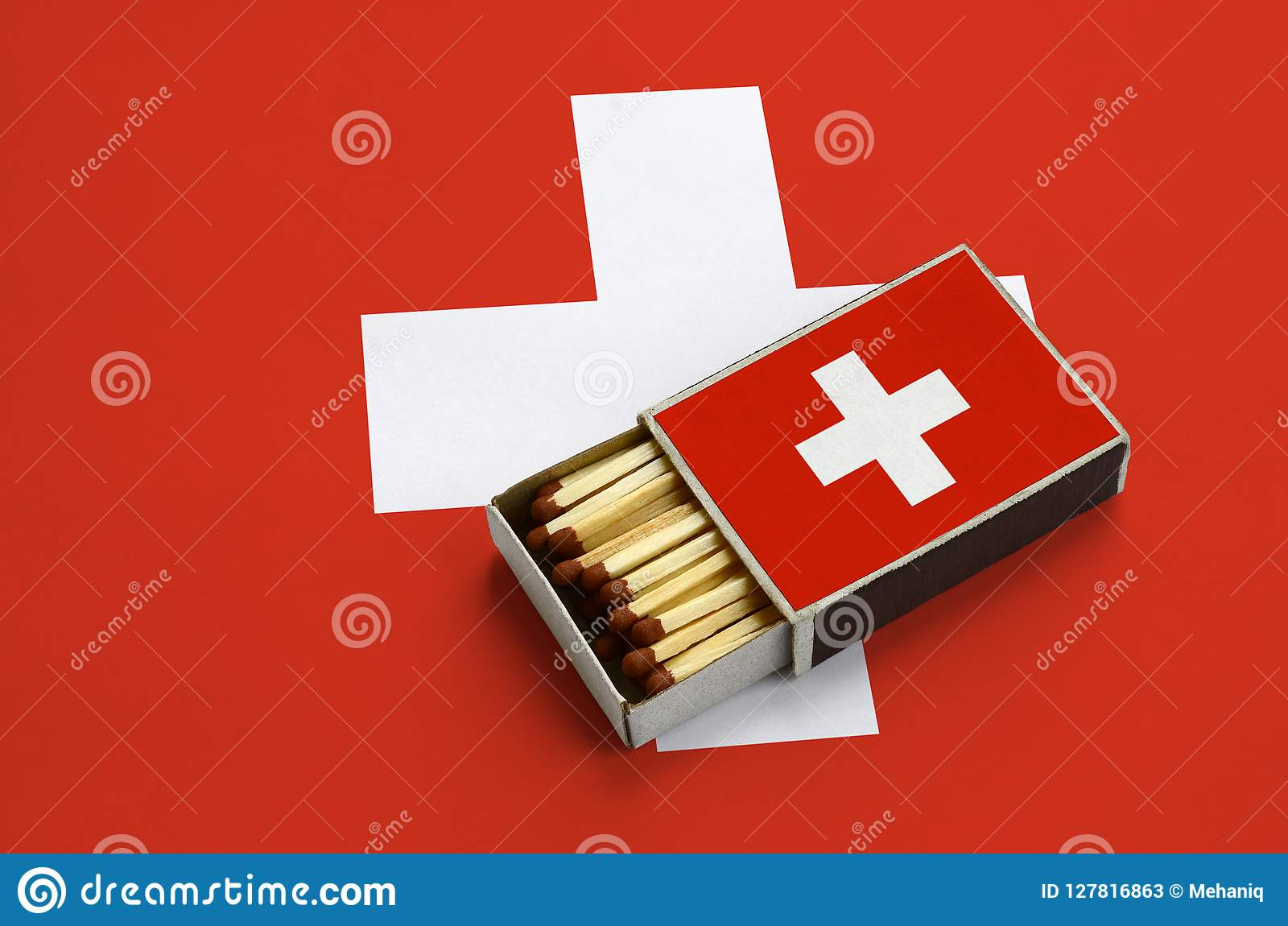 Le drapeau de la Suisse est montré dans une boîte d allumettes ouverte, qui est remplie de matchs et se trouve sur un grand drape