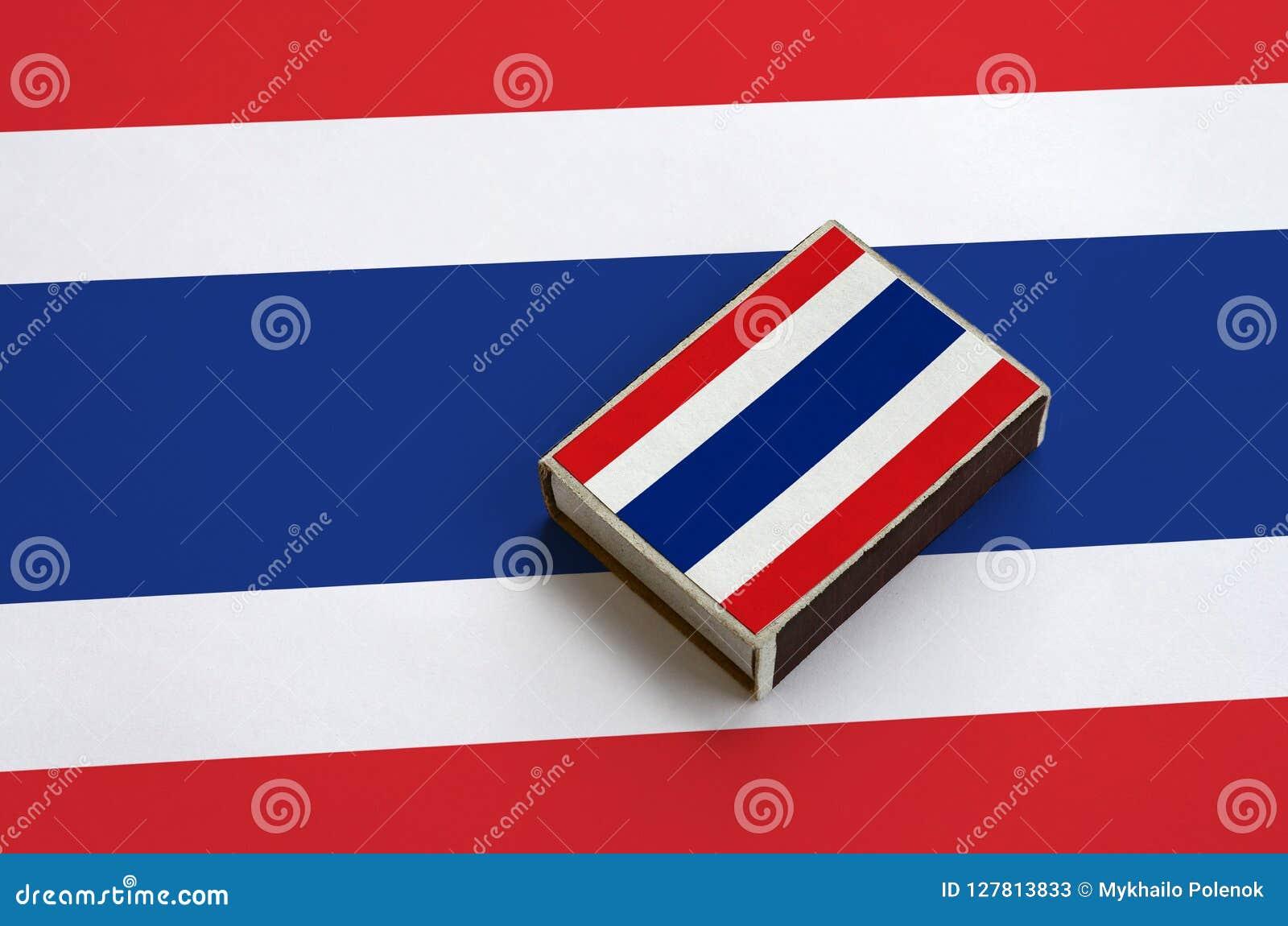 Le drapeau de la Thaïlande est décrit sur une boîte d allumettes qui se trouve sur un grand drapeau