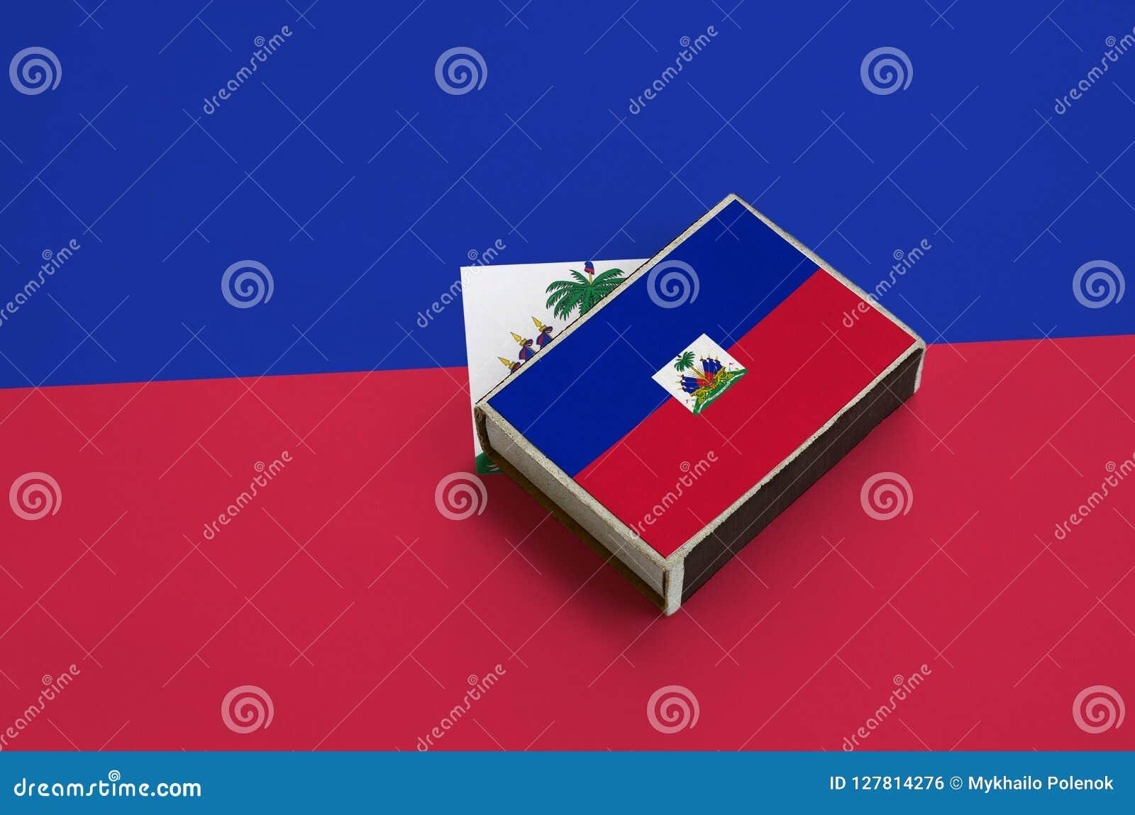 Le drapeau du Haïti est décrit sur une boîte d allumettes qui se trouve sur un grand drapeau