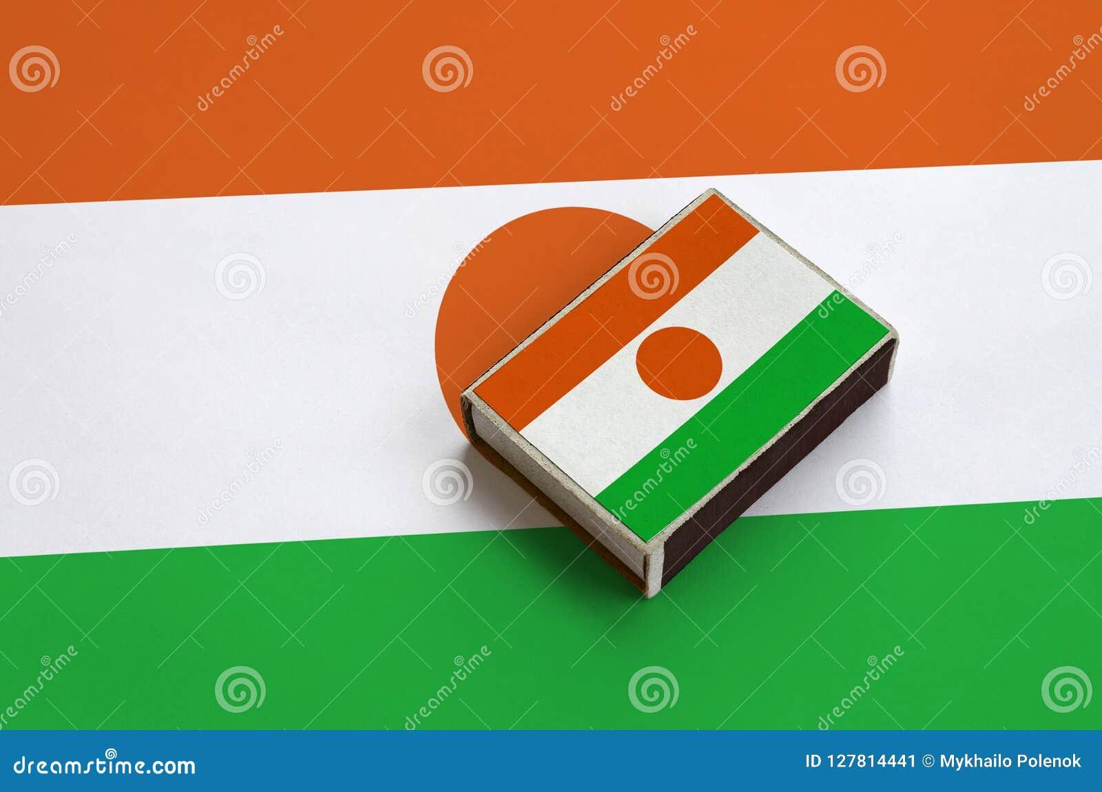 Le drapeau du Niger est décrit sur une boîte d allumettes qui se trouve sur un grand drapeau
