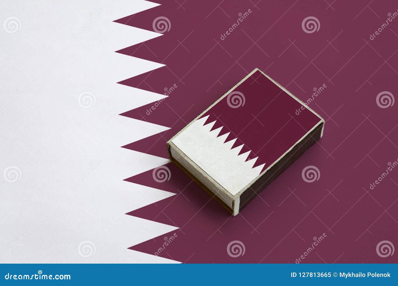 Le drapeau du Qatar est décrit sur une boîte d allumettes qui se trouve sur un grand drapeau