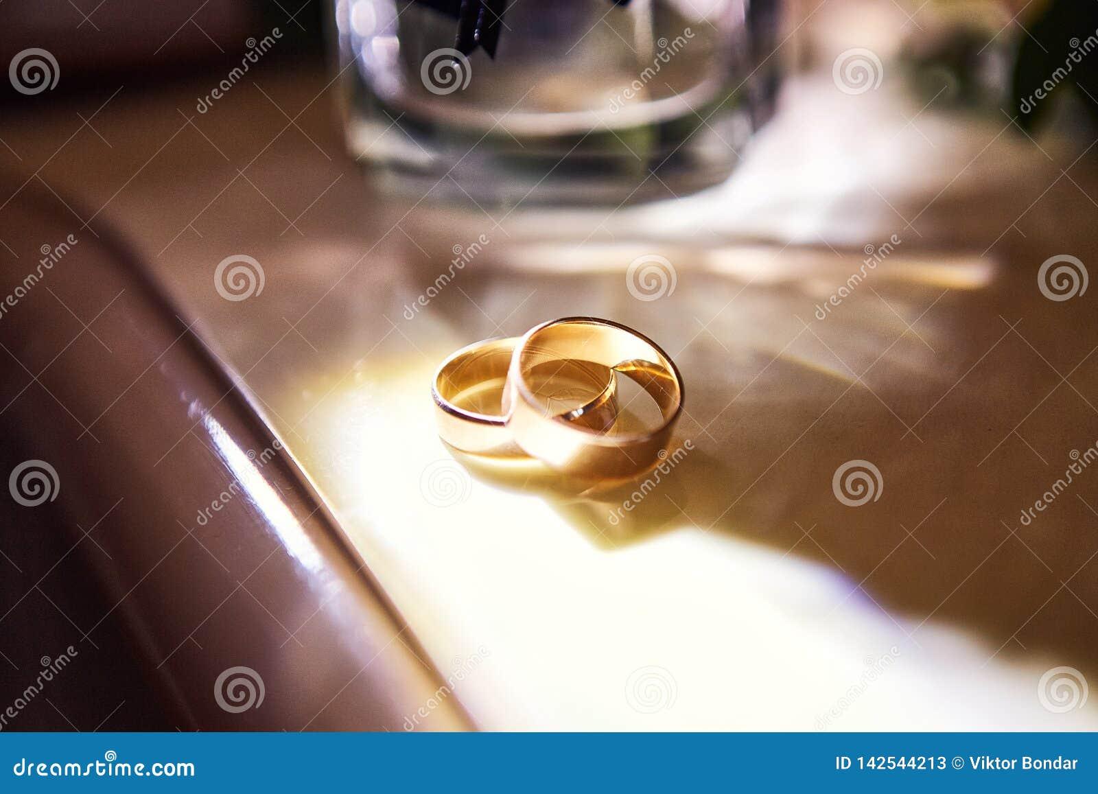 Le fedi nuziali si trovano sulla tavola vicino ad un mazzo di nozze